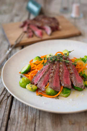 Flank steak in strips with carrot noodles and Brussels sprouts