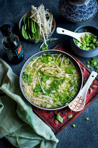 Asian-style egg soup with peas, sprouts, spring onion and soy sauce