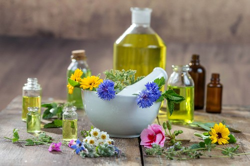 Various healing flowers, herbs and oils in and around a mortar