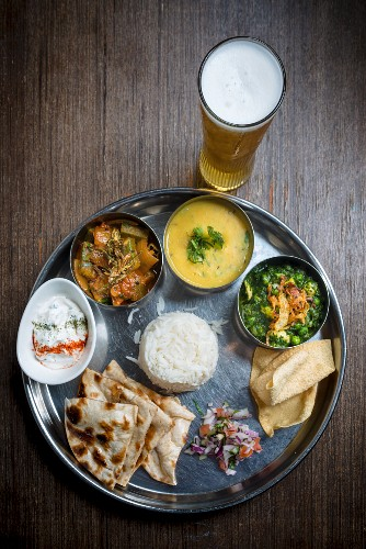 Vegetarian thali served with a glass of beer (India)
