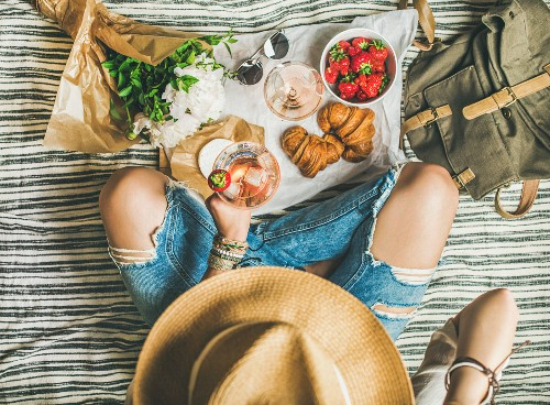 A woman wearing ripped jeans holding a glass of wine next to strawberries and croissants on a picnic blanket (seen from above)