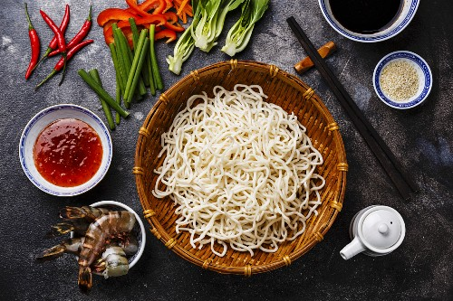 Raw Udon noodles in bamboo basket and Ingredients for cooking asian food with Tiger shrimps, greens, vegetables, spices on dark background