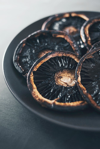 Fried portobello mushrooms on a black plate