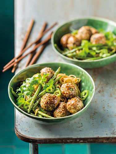 Sesame meatballs on noodles with green beans, chili and coriander