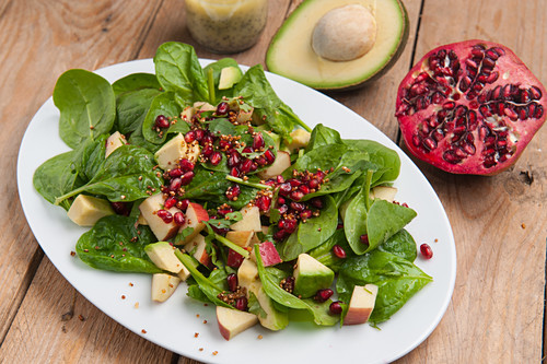 A superfood salad with baby spinach, avocado, apple, quinoa and pomegranate seeds