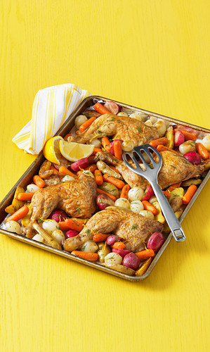 Chicken legs with vegetables on a baking sheet