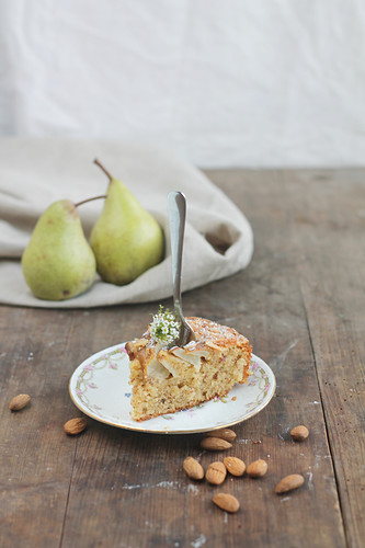 A slice of pear and almond cake with a fork, on a wooden table with a linen cloth