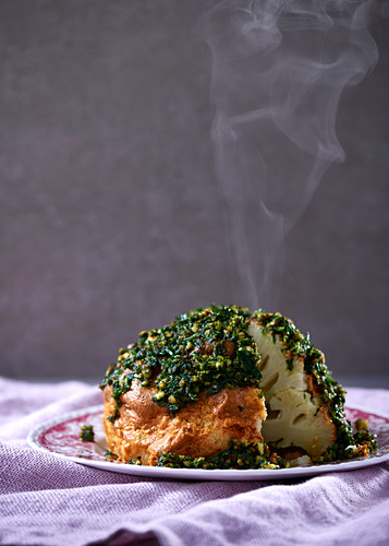 A whole cauliflower in a Tahini spice crust with almond and herb pesto