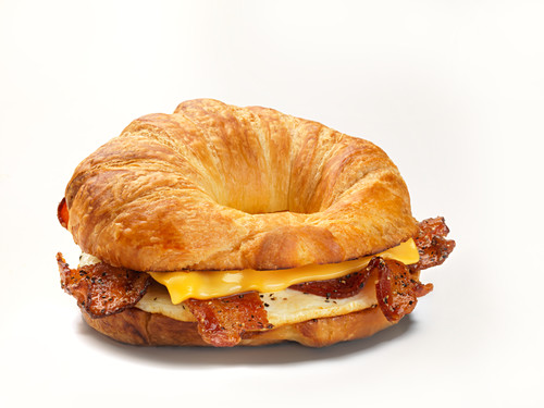 A croissant bagel with bacon, fried egg and cheese