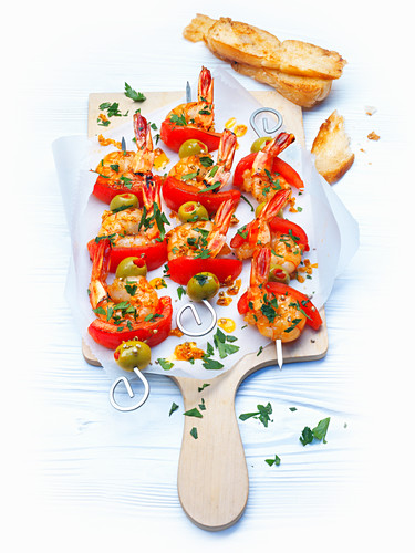 Scampi skewers with tomatoes and olives