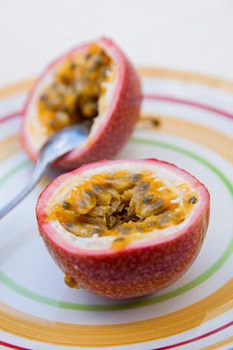 Halved Passion Fruit on colorfull plate with spoon