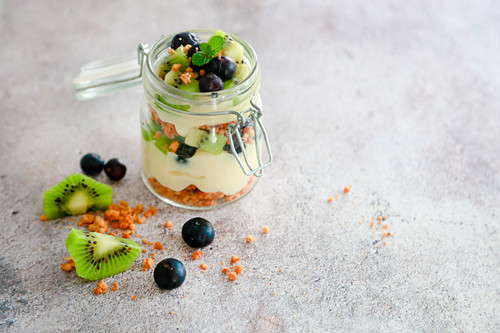 Quick layered dessert with biscuit crumbs, custard cream and fruit