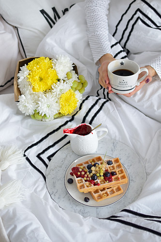 Breakfast in bed with coffee and waffles with fresh berries