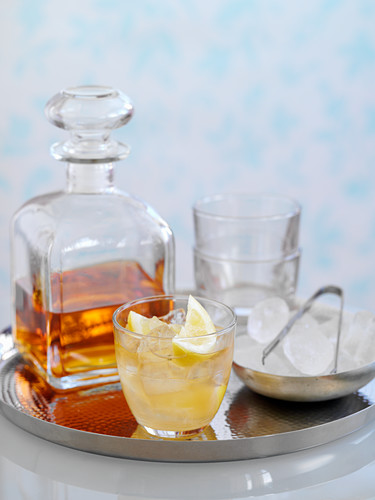 A whiskey cocktail with ice and lemon wedges