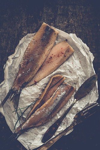 Herring fillets with chives and pink pepper on parchment paper with a knife and fork