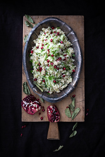 Vegan bulgur salad with cucumber and pomegranate seeds flavoured with kaffir lime leaves