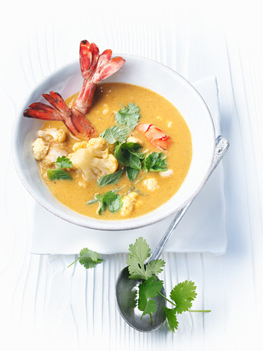 Coconut and cauliflower soup with prawns and herbs