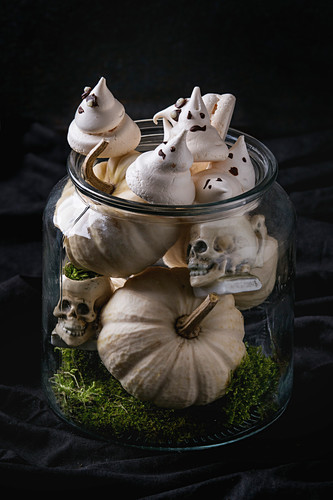 Halloween: jar with white meringue ghosts with chocolate eyes, decor skulls, moss and pumpkin over black background