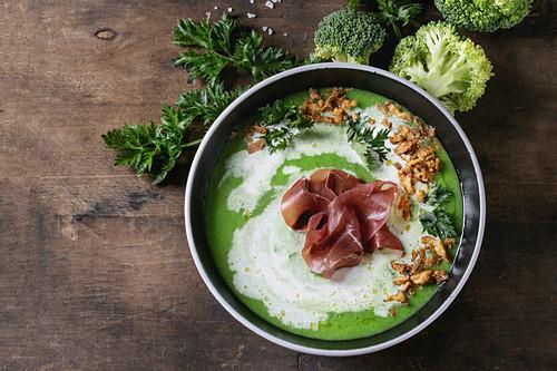 Vegetable broccoli cream soup served with italian bresaola ham, cream, fried onion, fresh parsley and broccoli