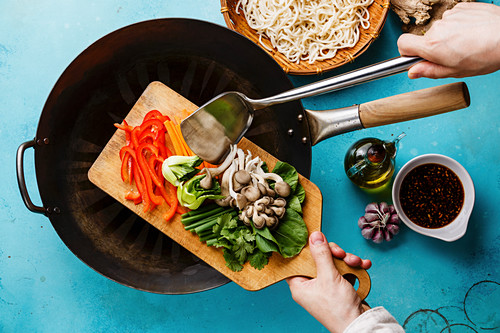 Cooking process Udon noodles with oyster mushrooms and vegetables and male hand on blue background