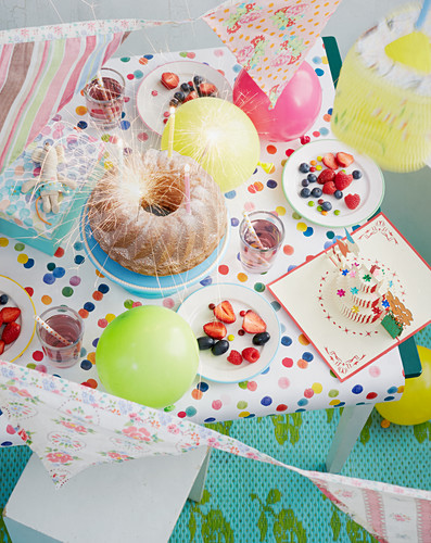 A table laid for a child's birthday part with cake, fruit and drinks