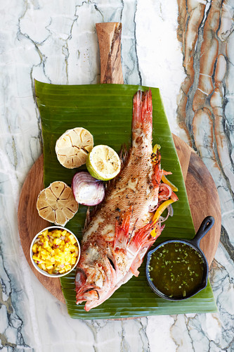 Roasted red mullet with garlic on a banana leaf