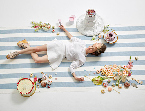 A woman lying on the floor with a paintbrush in her hand, surrounded by doughnuts and cakes