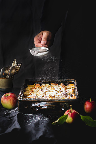 Bread and apple pudding being dusted with icing sugar