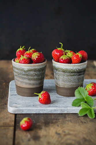 Strawberries in bowls on a marble board