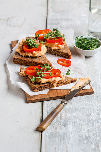 Open hummus sandwiches with pointed peppers and garden cress