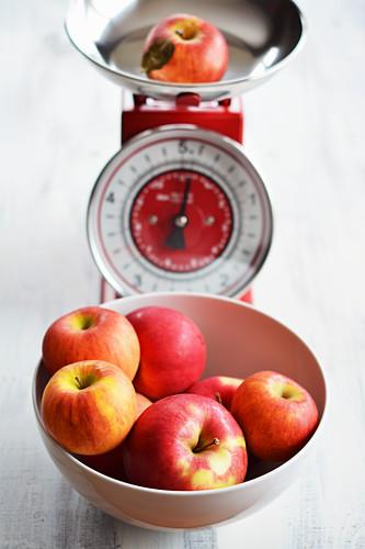 Rote Äpfel in Schüssel und auf nostalgischer Küchenwaage