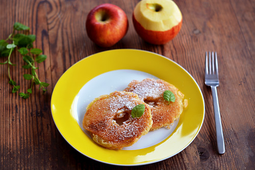 Two battered apple rings with sugar, cinnamon and mint on a yellow plate