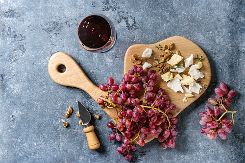 Wooden serving board with fresh red grapes, walnuts, goat and cheddar cheese, with cheese knife and glass of red wine
