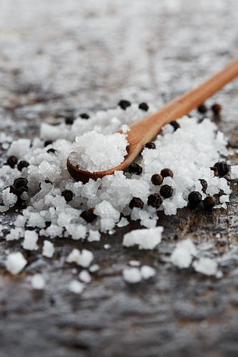 Sea salt and black peppercorns with a wooden spoon