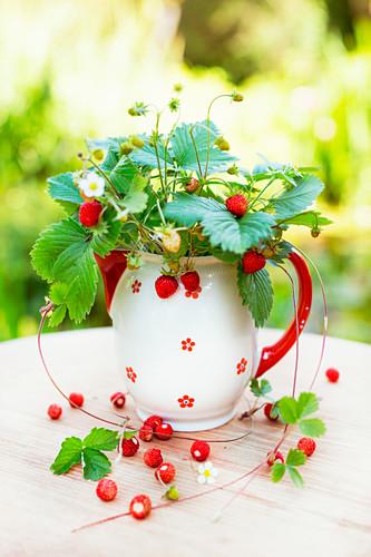 Posy of freshly picked wild strawberries in vintage ceramic jug on wooden table in garden