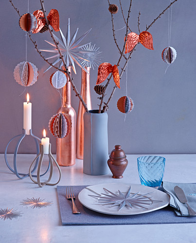 Christmas place setting, ornaments, candles and modern baubles hung from branches on table