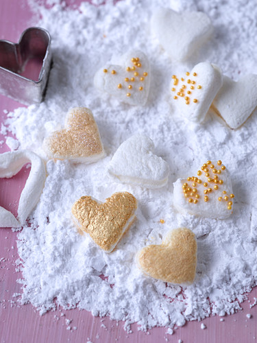 Marshmallow hearts decorated with gold beads, in powdered sugar