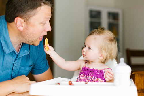 A little girl in a high chair feeding her father