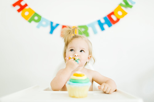 A little girl sitting in a high chair and eating a muffin for her first birthday