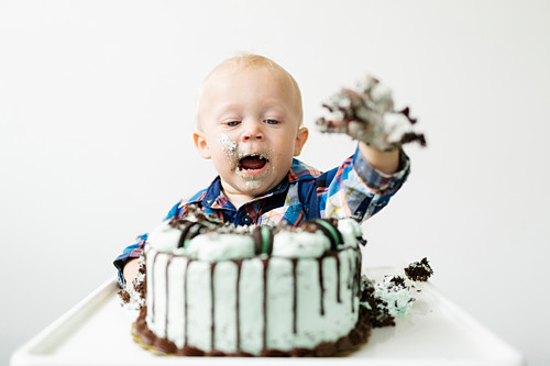 A little boy sitting in a high chair and eating a birthday cake