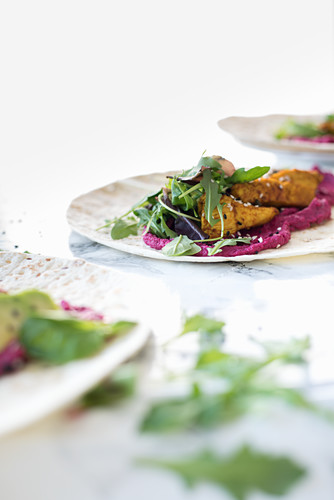 Wholegrain wraps with beetroot hummus, avocado, turmeric chicken, sesame seeds and rocket