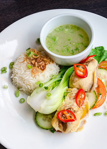Thai chicken thighs with fresh chilly, cucumber and tomato salad, white basmati rice and spring onion broth on a white plate