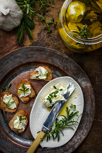 Marinated labne balls with herbs served on toast