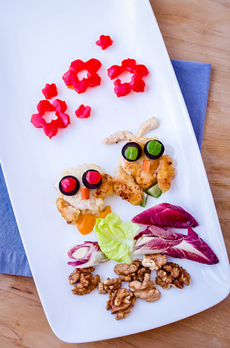 Owls made of grilled chicken breasts, black olives, peppers, endive and chicory leaves, walnuts on a white plate with a blue napkin