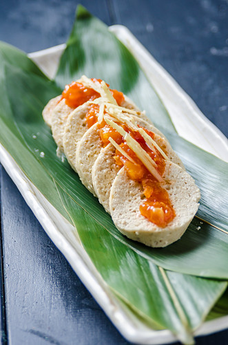 White chicken meat spicy sausage with a mango and chilli sauce on a white plate with decorative leaves on a blue background