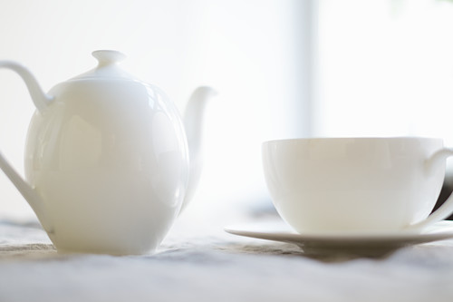 A place setting for coffee with a coffee pot