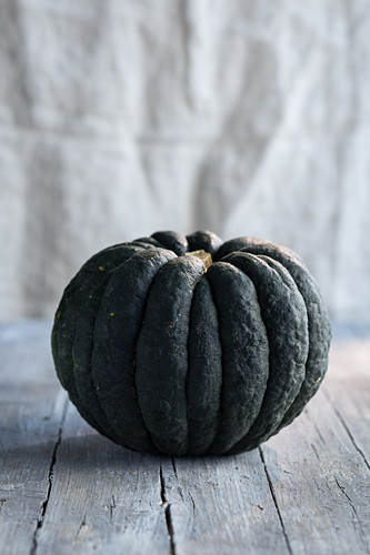A dark green pumpkin on a wooden table
