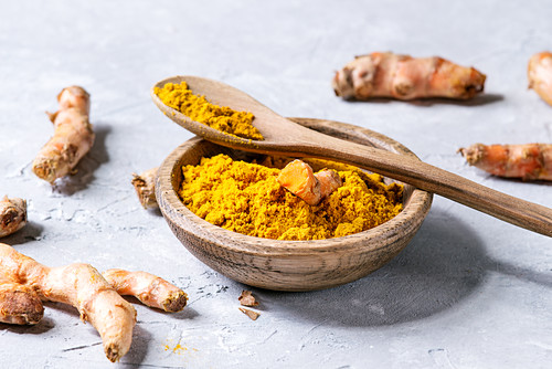 Turmeric roots and powder in wooden bowl over gray concrete background