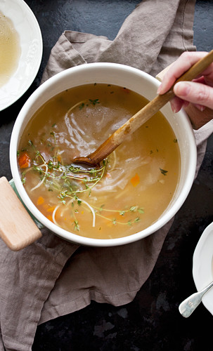 A woman's hands stirring a pot of chicken noodle soup with a wooden spoon