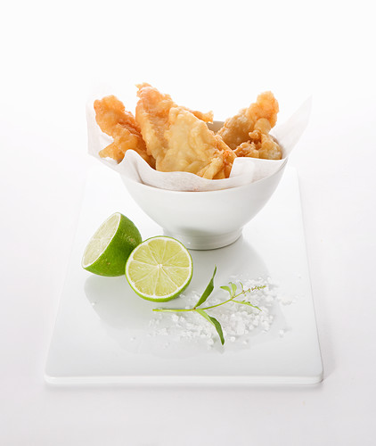 Battered fish in a bowl with lime halved, sea salt and sprig of fresh lime leaves